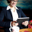 Young businesswoman using her tablet computer on a coffee break. - Stock Photo
