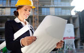 Young female architect/construction engineer reviewing plans at — Stock Photo