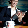 Stock Photo: Beautiful businesswoman using tablet computer on coffee break