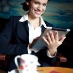 Beautiful businesswoman using tablet computer on coffee break — Stock Photo