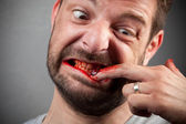 Crazy nailbiter. A man biting of his nails — Stock Photo