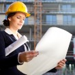 Construction specialist looking at blueprints at construction si - Stock Photo