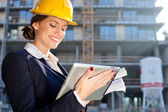 Attractive female construction specialist with a tablet computer — Stock Photo
