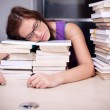 Beautiful young woman falling asleep on stacks of books in the l — Stock Photo