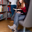 Beautiful young woman sitting in a lounge chair in the library r — Stock Photo