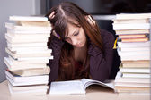 Student buried in books. Studying in the library — Stock Photo