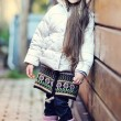 Cute child girl with long dark hair poses outdoors — Stock Photo