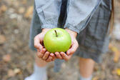Hands of a child girl holding a green apple — Stock Photo