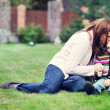 Young mother kisses her daughter on the lawn — Stock Photo #6782530
