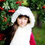 Cute little girl in fur coat under rowan tree — Stock Photo