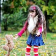Cute little girl wearing fur coat in autumn forest — Stock Photo #6850590