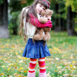 Cute little girl wearing fur coat in autumn forest — Stock Photo #6850597