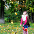 Cute little girl wearing fur coat in autumn forest — Stock Photo