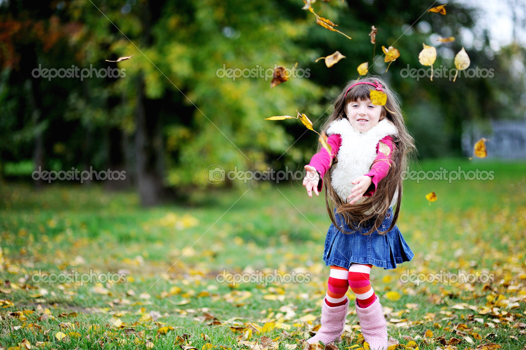 Adorable little brunette girl in pink outfit jumping with yellow leaves  Stock Photo #6850607