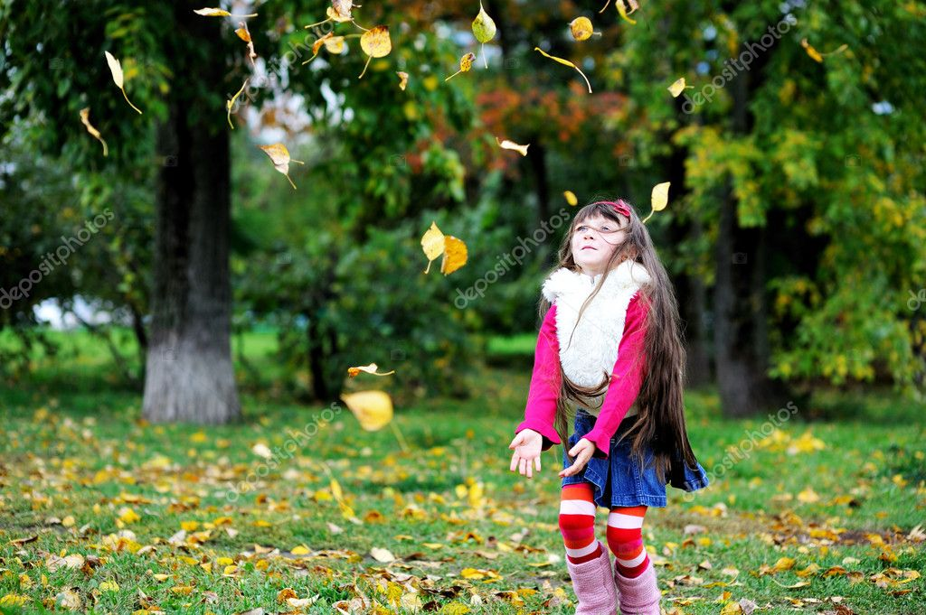 Adorable little brunette girl in pink outfit jumping with yellow leaves — Stock Photo #6850612