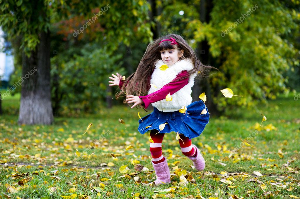 Adorable little brunette girl in pink outfit jumping with yellow leaves — Stock Photo #6850622