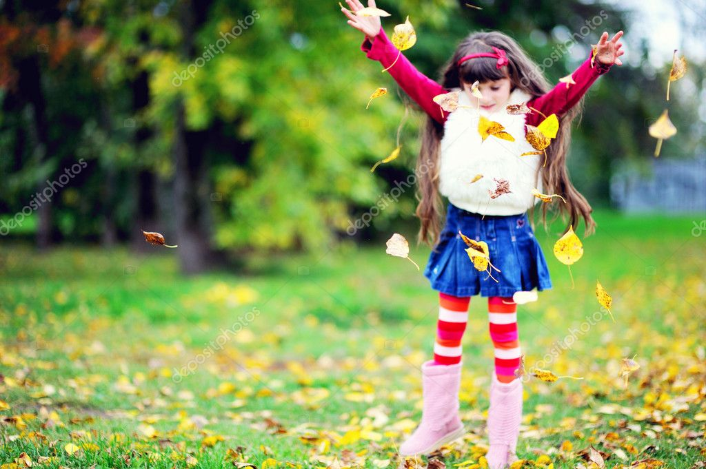 Adorable little brunette girl in pink outfit jumping with yellow leaves — Stock Photo #6850623