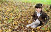 Cute child girl sitting on carpet of autumn leaves — Stock Photo