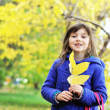 Portrait of smiling little girl with yellow leaves — Stock Photo
