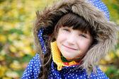 Portrait of cheerfull child girl in blue coat — Stock Photo