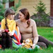 Young mother sitting with daughter on a lawn - Stock Photo