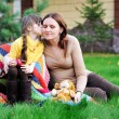 Foto Stock: Young mother sitting with daughter on a lawn