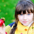 Funny child girl eating apple outdoors — Stock Photo