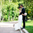 Bride and groom walking in a summer park — Stock Photo
