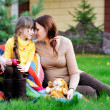 Young mother sitting with daughter on a lawn — Stock Photo #7191663
