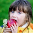 Funny child girl eating apple outdoors - Stock Photo
