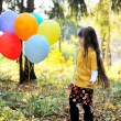 Child girl with balloons in autumn forest — Stock Photo #7193542