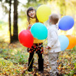 Little boy and girl with balloons in forest — Foto de stock #7193544