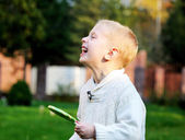 Funny little boy with big lollipop laughing — Stock Photo