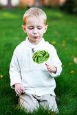маленький мальчик с большой леденец на зелёной лужайке — Стоковое фото
