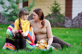 Young mother sitting with daughter on a lawn — Stock Photo