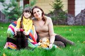 Jeune mère assise avec fille sur une pelouse — Photo