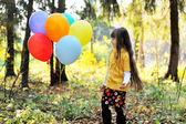 Child girl with balloons in autumn forest — Stock Photo
