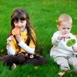 Little friends eating lollipops together on a lawn — Stock Photo #7321606
