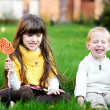 Stock Photo: Little friends eating lollipops together on lawn