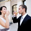 Royalty-Free Stock Photo: Bride and groom drinking champagne outdoors