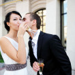 Bride and groom drinking champagne outdoors — Stock Photo