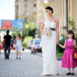 Beautiful bride posing together with flowergirl — Foto Stock