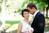 Bride and groom standing together in a park — Stock Photo