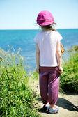 Liten flicka i rosa solhatt ute vid havet — Stockfoto