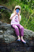 Little girl with mobile phone on rocks — Fotografia Stock