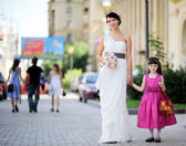 Beautiful bride posing together with flowergirl — Stock Photo