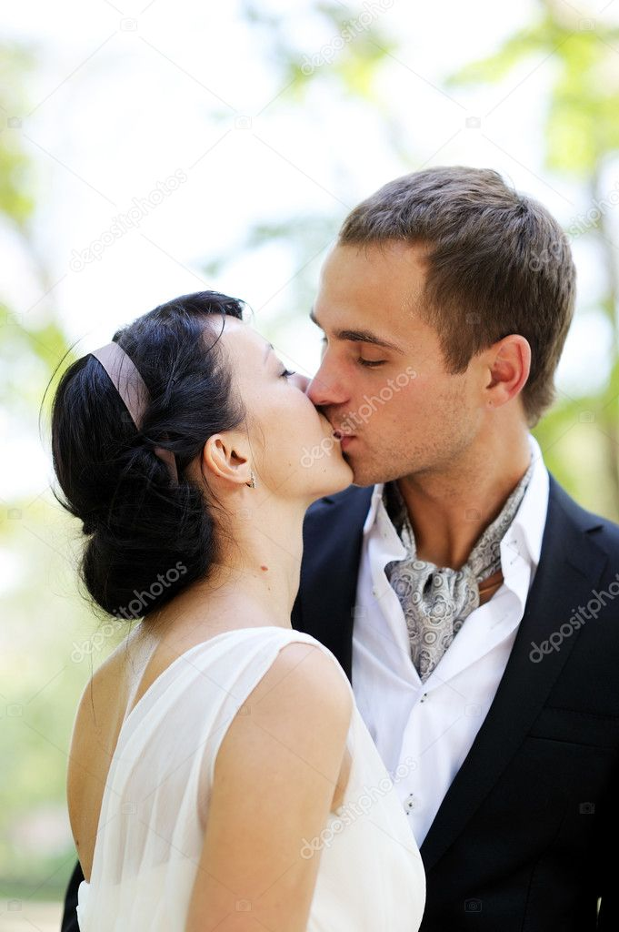 Bride and groom kissing outdoors in the park — Stock Photo #7533991