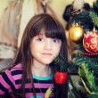Portrait of little girl under Christmas tree — Stock Photo