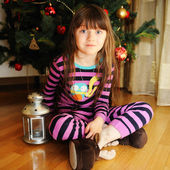Portrait of little girl under Christmas tree — Stockfoto