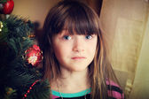 Portrét holčička pod vánoční stromečekクリスマス ツリーの下の小さな女の子の肖像画 — ストック写真